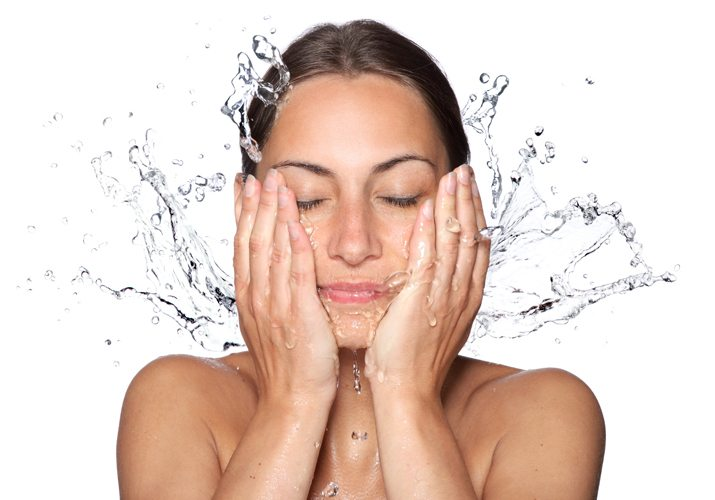 Women splashing water on her face after using Clarisonic to cleanse her skin