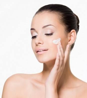 women applying exfoliating scrub to her face to cleanse her skin and pores