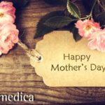 Mother's day card with pink and white flowers resting on wooden table.