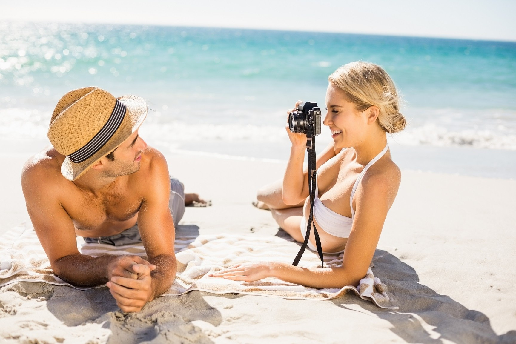 Young couple laying on a sunny beach taking photograph. with the ocean in background.