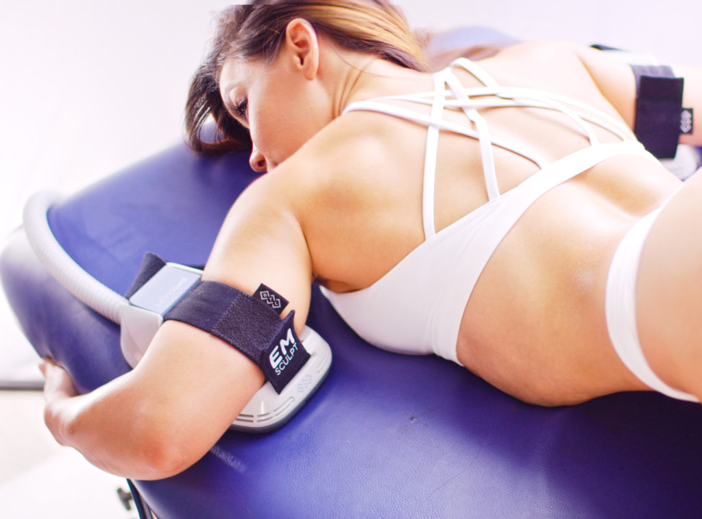 woman laying on her stomach receive the emsculpt treatment on her upper arms