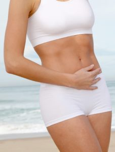 Woman with toned stomach standing at the beach.
