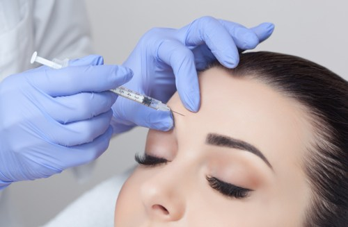 Brunette woman getting dysport injection between the eye brow area.