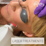 Esthetician using laser facial treatment on client's cheek