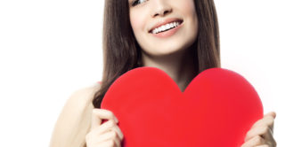 Beautiful young woman in red holding paper heart