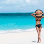 woman standing on sandy beach looking at blue ocean