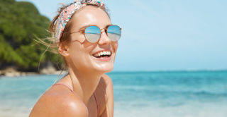 Young blonde woman wearing sunglasses on beach