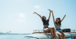 two woman waving their arms while sitting on top of VW van at the beach