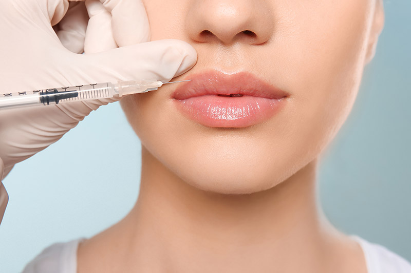 Close up of bottom half of young womens face as she gets lip injections from a doctor
