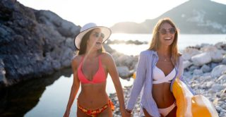 two young women on a beach during the summer laughing and having fun