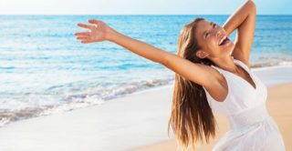 Freedom woman on beach enjoying life with open arms feeling free bliss and success on beach. Happiness Asian girl in white summer dress enjoying ocean