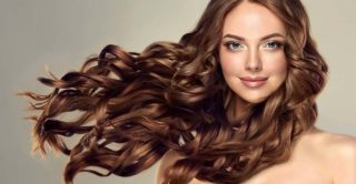 Beauty brunette women with long and thick and healthy shiny wavy hair . B