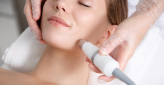 women laying down looking peaceful while having laser skin treatment on her face