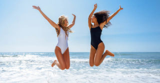 two young women smiling and jumping in the air at the beach