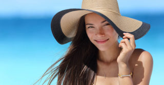 young women on beach wearing a big sun hat to protect her skin from sun damage