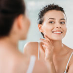 young women smiling and looking in the mirror with radiant flawless skin