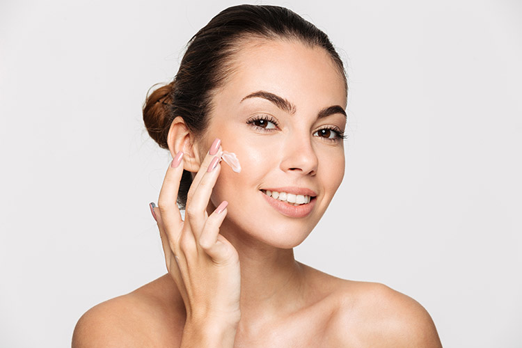 women applying skincare product to face to help enhance the long-term results of a cosmetic treatment