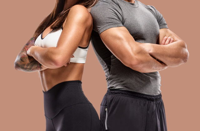 toned couple in workout clothes standing back to back with arms crossed