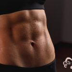 Close up of fit female abs isolated on black background